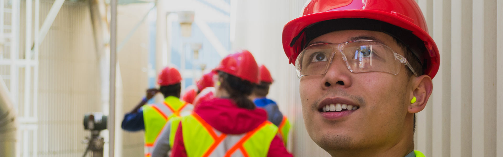 Marc in a hard hat looking up during an chemical plant tour