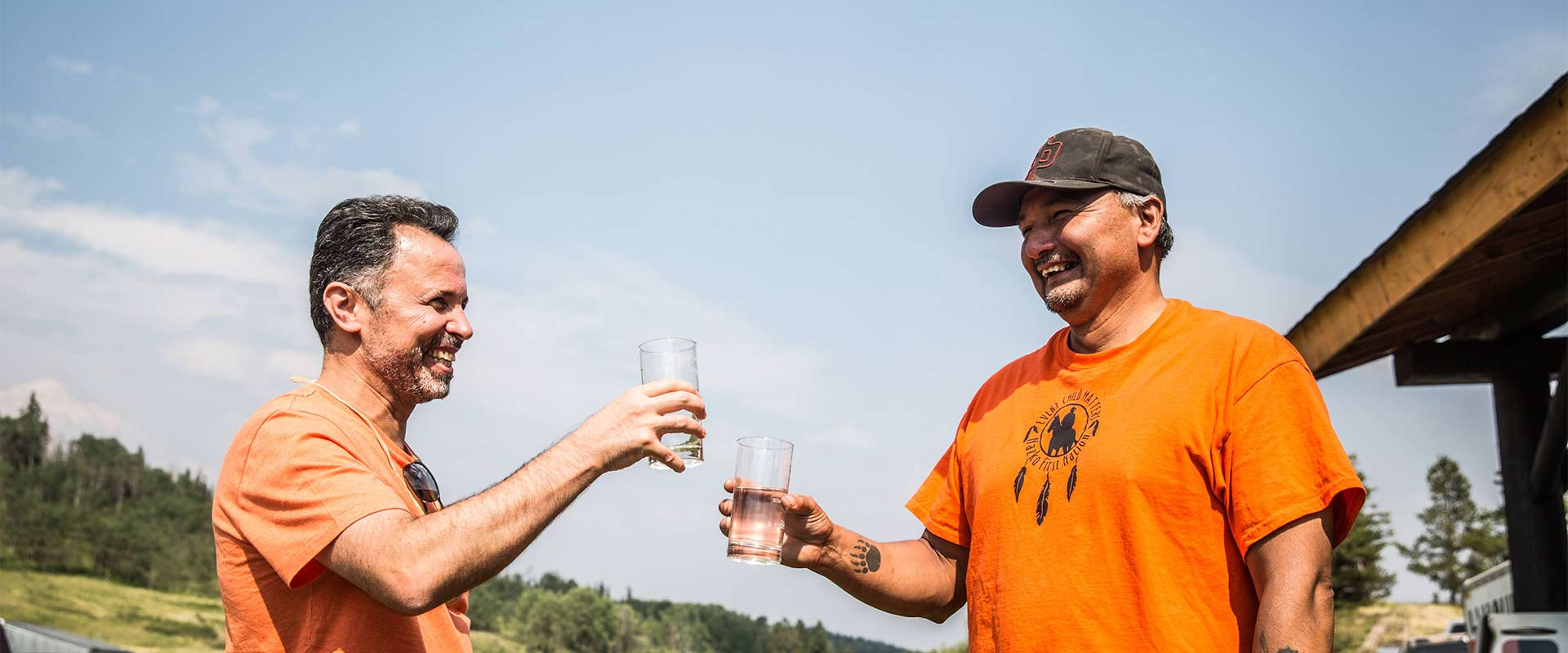 Professors in orange shirts raise their glass to toast