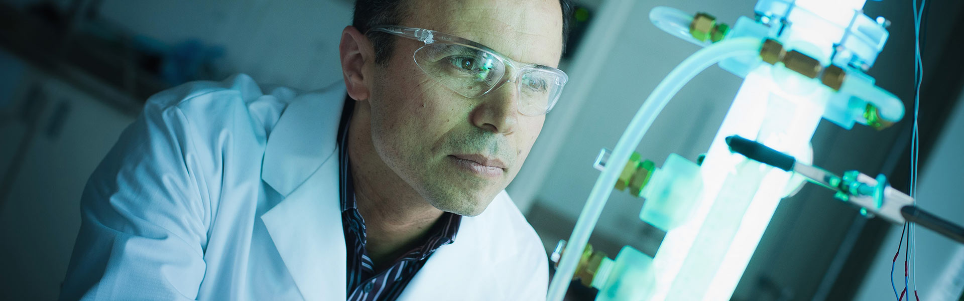 Dr. Mohseni looks into a lab apparatus